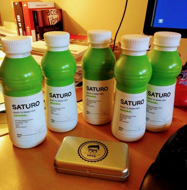 Cinq bouteilles de Saturo Original sur un bureau