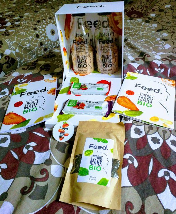 La boîte du lancement de la gamme bio de Feed : livret, bloc-note, sachet de graines de basilic, autocollants, badges, et bien sûr poudres et barres.